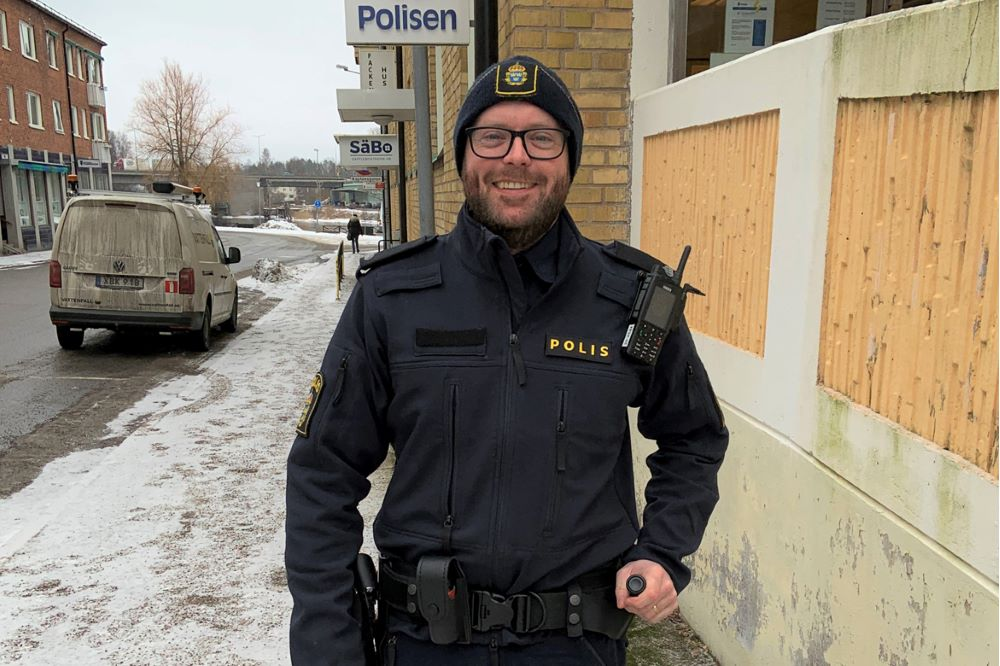 Person i polisuniform utanför polisstation.