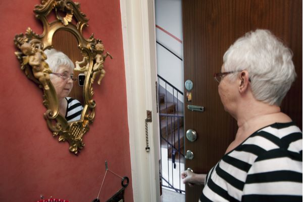 Elderly woman opens her door